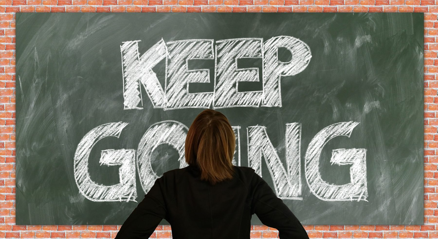 "Woman looking at blackboard with ""Keep Going"" written."