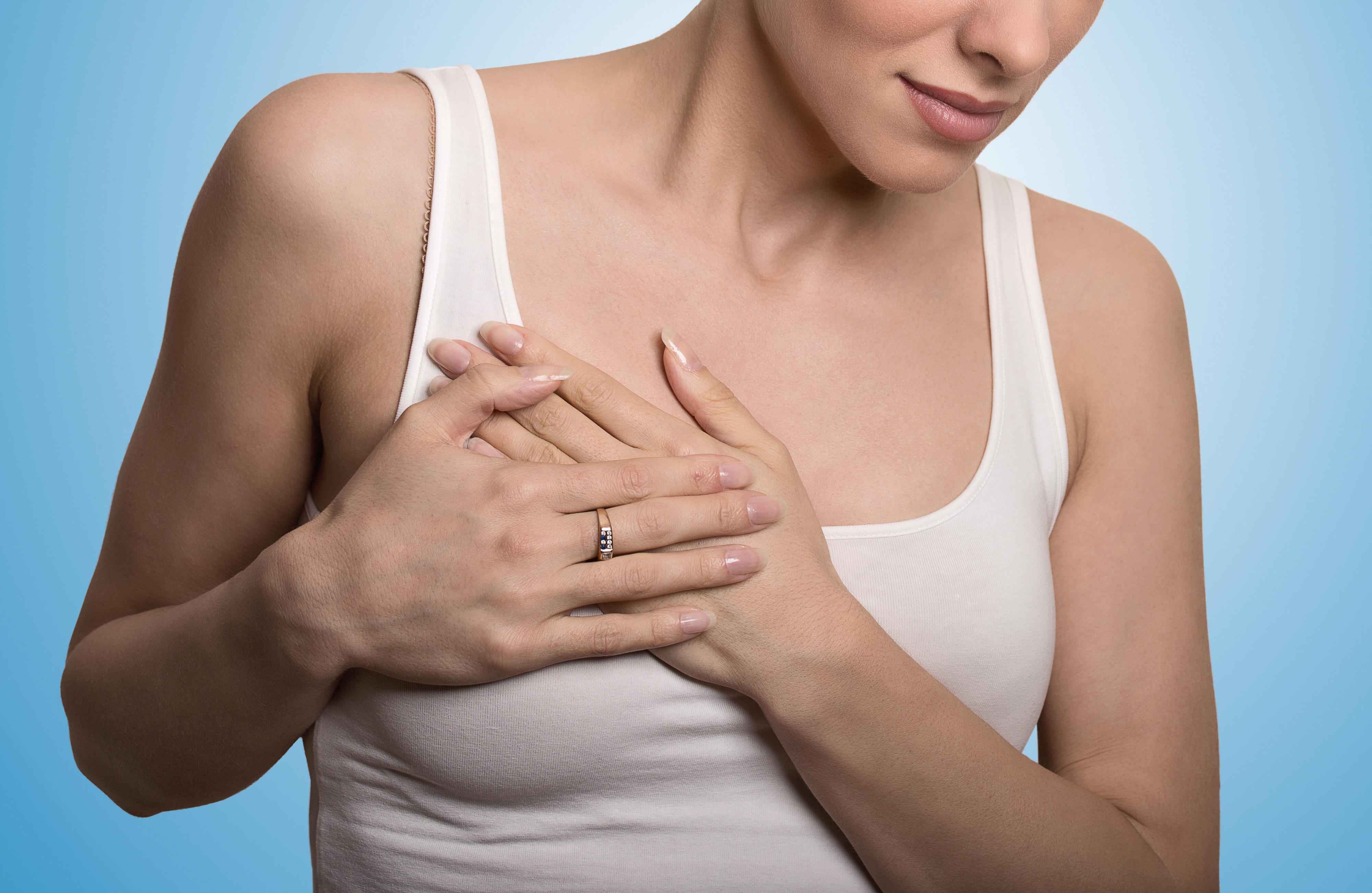 Woman with hands over breast area.
