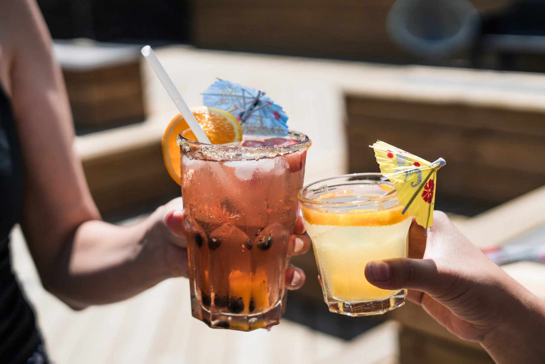 Close-up of two drinks of alcohol with colorful umbrellas.
