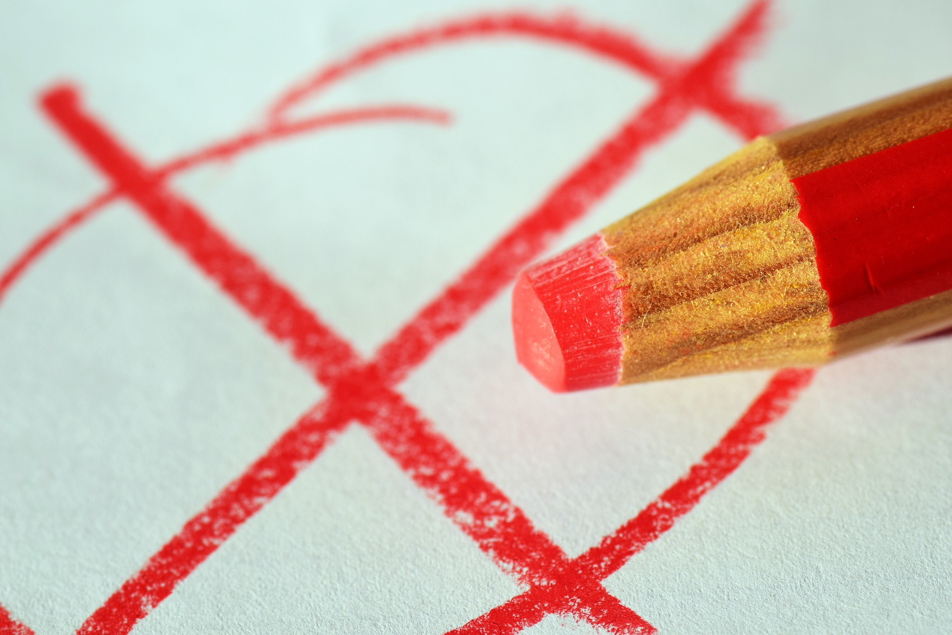 Red pencil marking an X over items that do not belong in a functional policy.