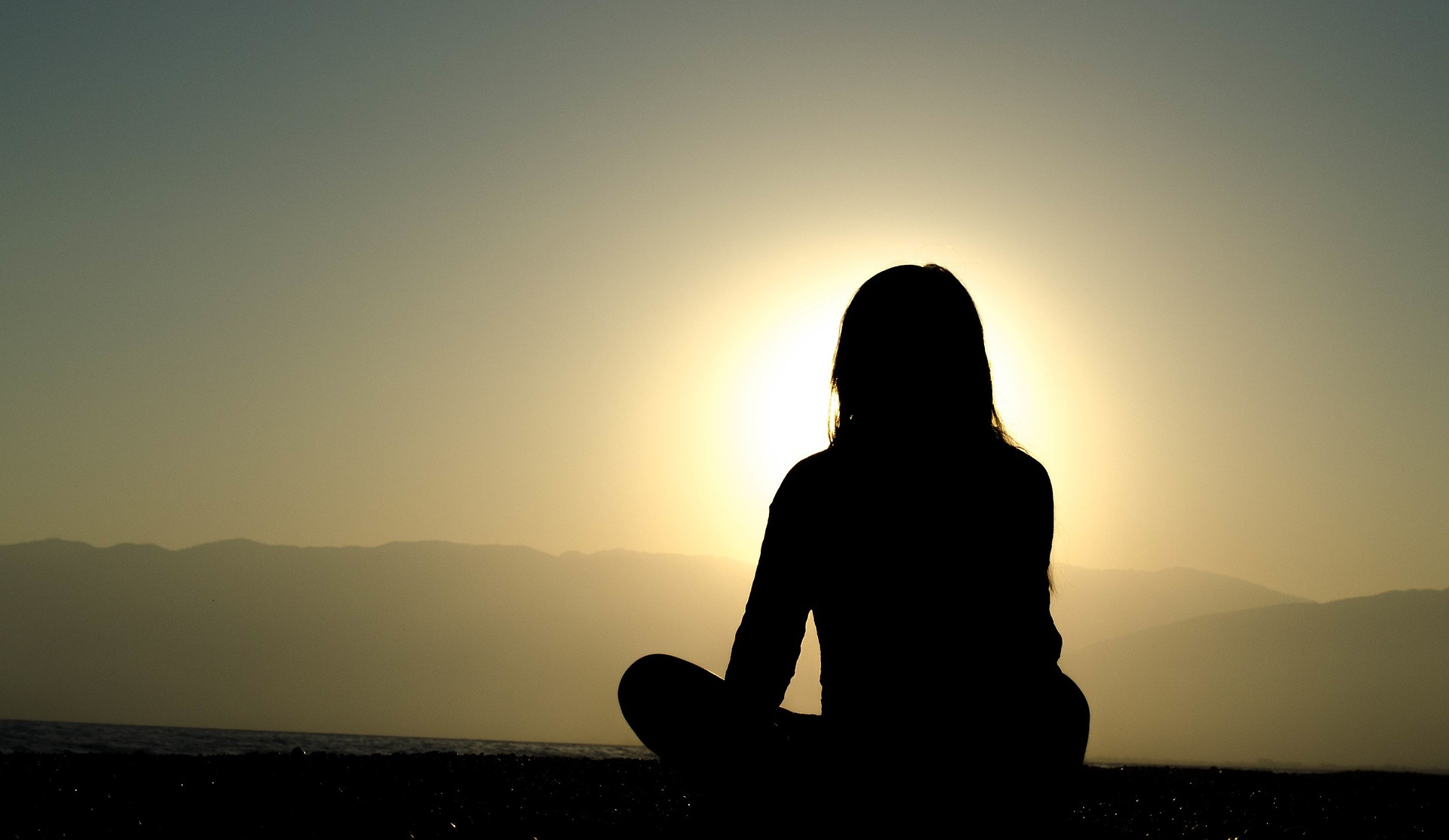 Woman sitting atop a mountain overlooking peaceful surroundings.