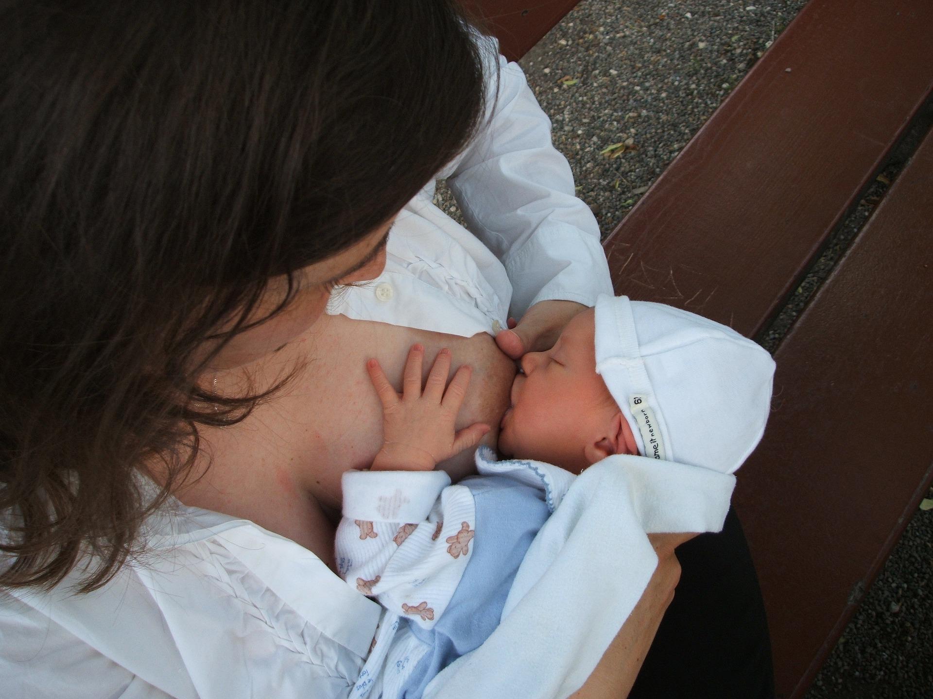 Mother feeding her child human milk,