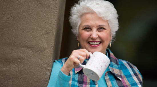 Picture of Marie Biancuzzo holding a mug, smiling.