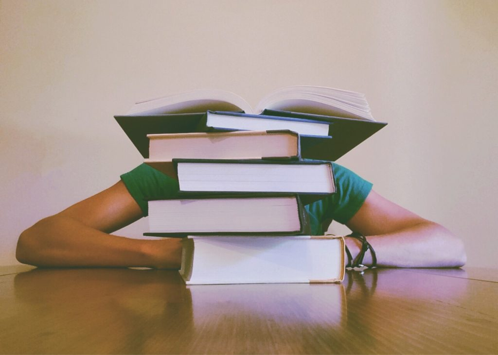 Woman behind stack of books to study.