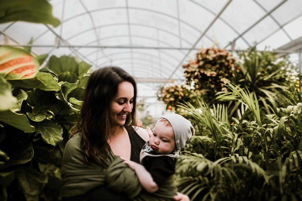 Mom babywearing in a greenhouse.