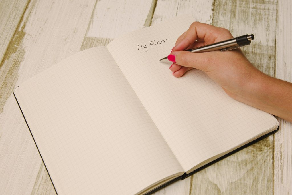 Blank notebook with the words My Plan at the top with a hand