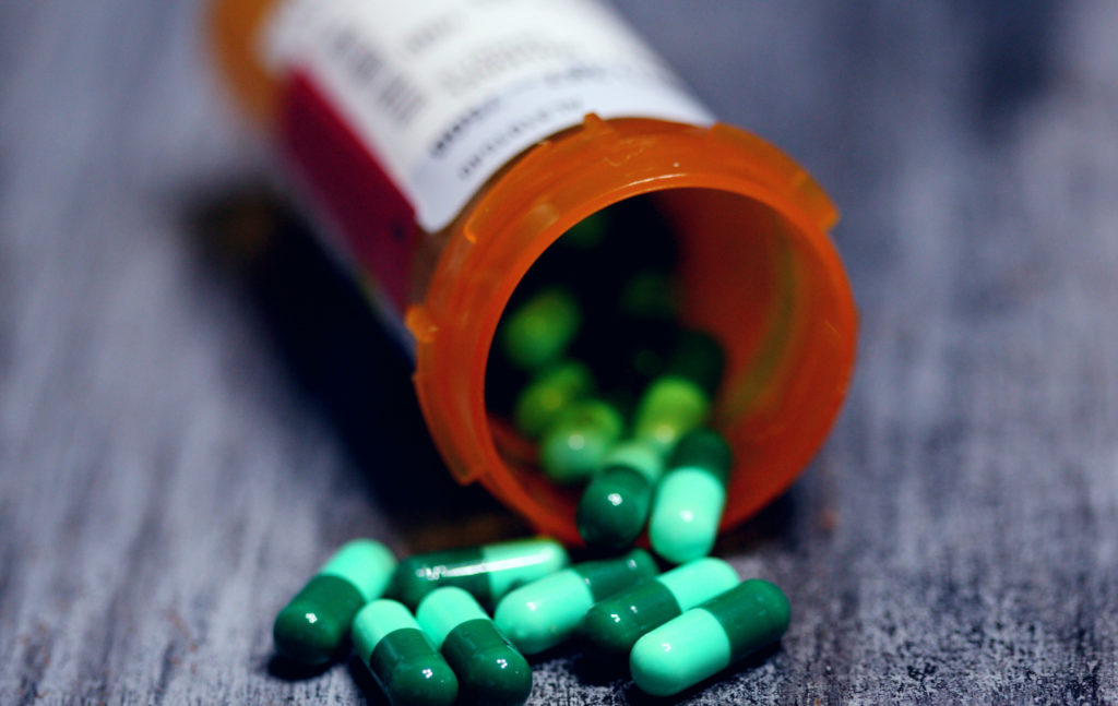 Prescription medications bottle spilling out capsules.