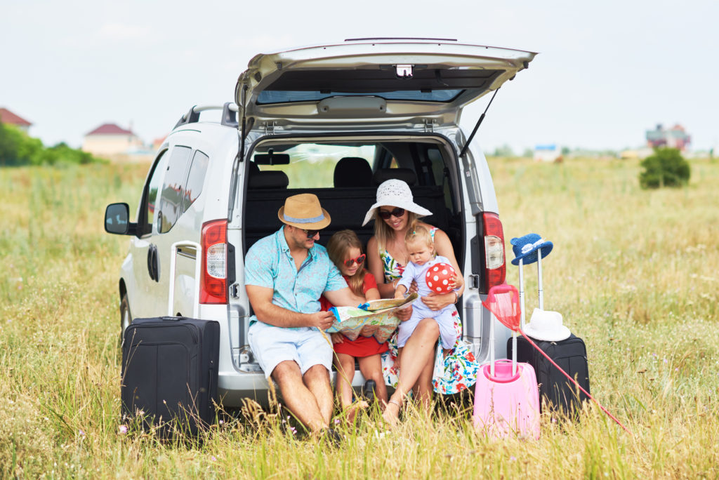 Family with suitcases on road trip with a nursing baby.