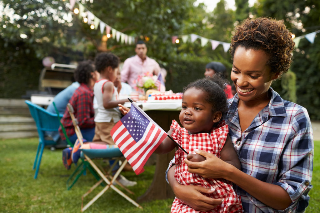 Mother and daughter holding flag at backyard party