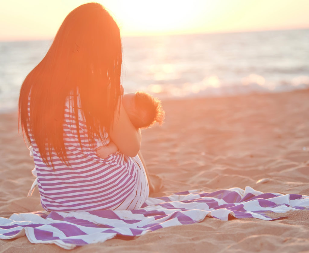 Woman breastfeeding on beach; breastfeeding makes for healthier moms and babies