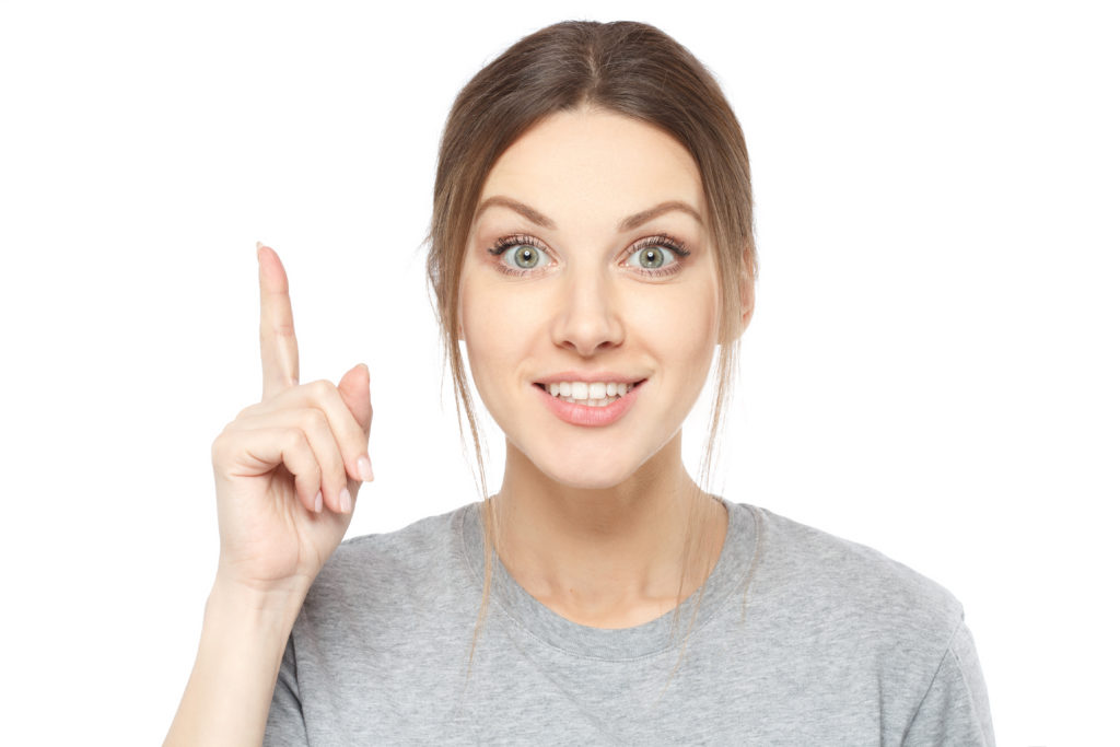 Woman with a pointed finger with the secret of getting the right answer on application-level questions.