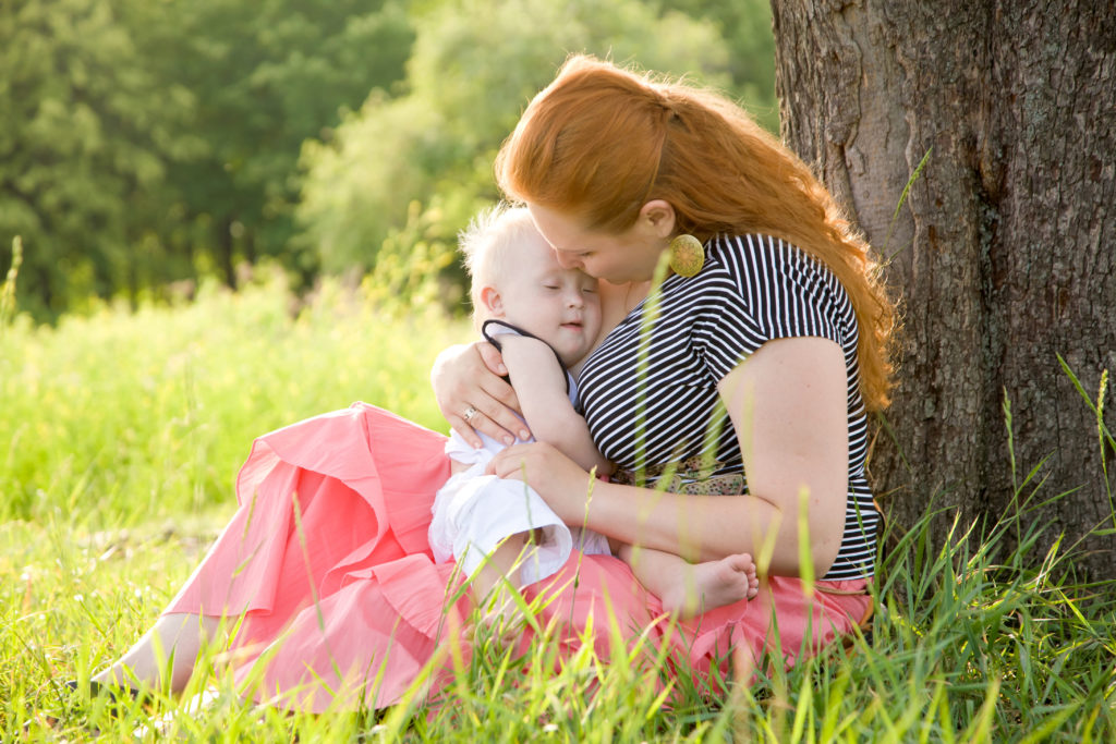 Redheaded woman holding baby with Down Syndrome in a field of grass.