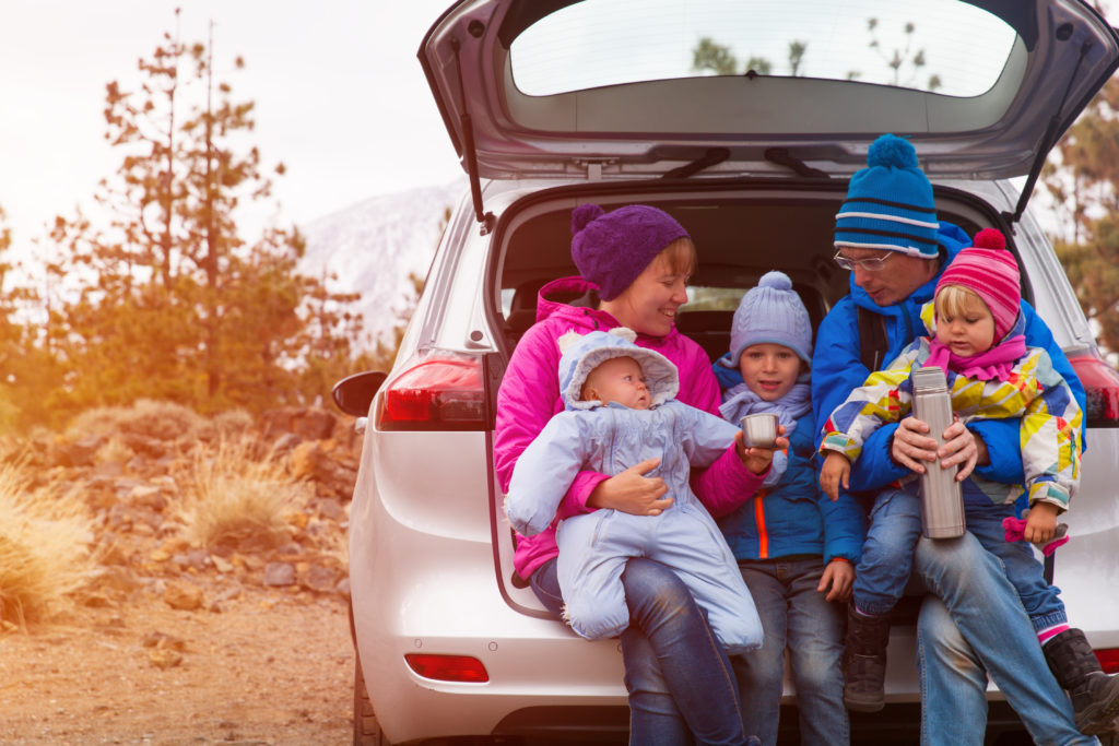 Family in winter clothing traveling in a car with a thermos.