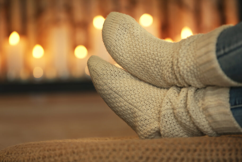 Slipper sock covered feet relaxing in front of candles.