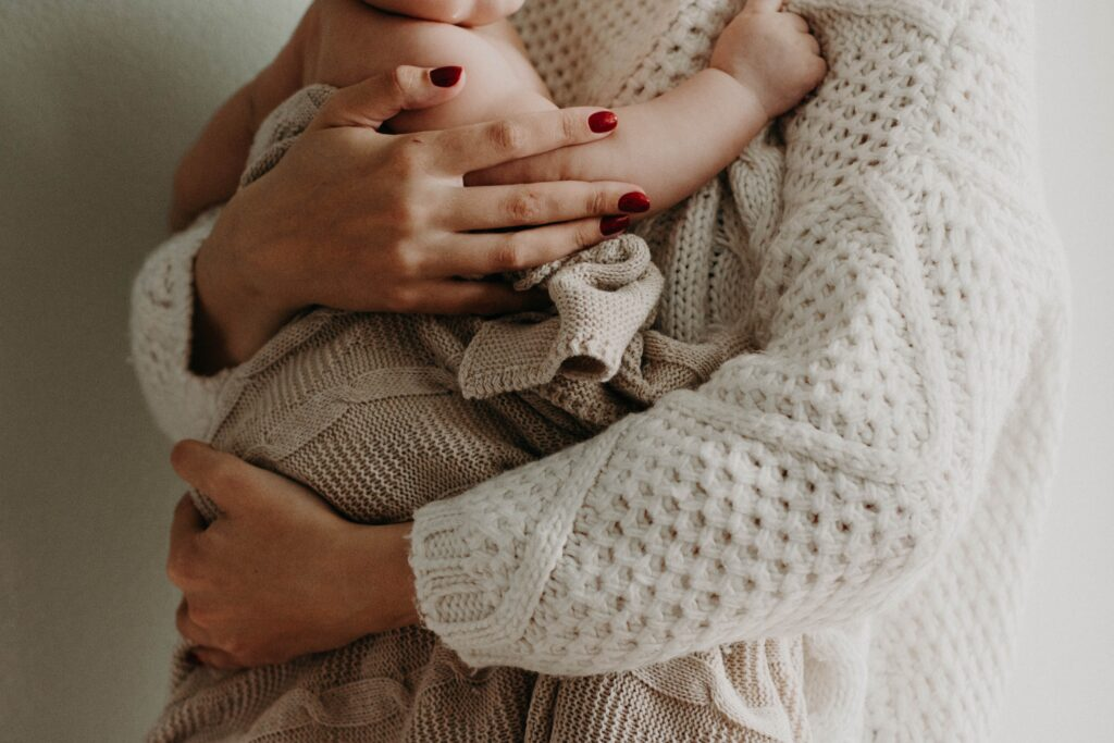Mom in white sweater holding baby