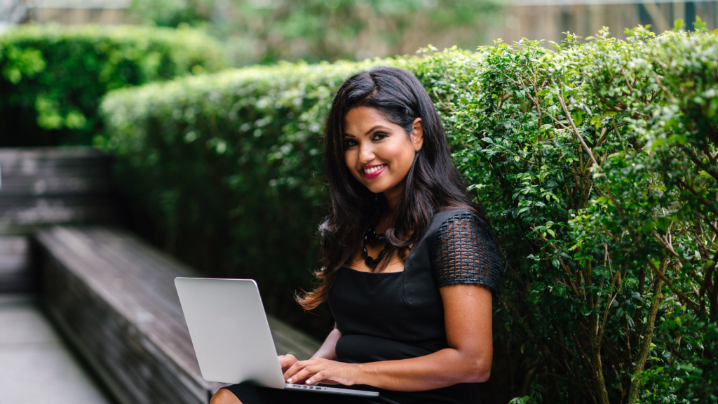Woman in black dress sitting outside with laptop computer.