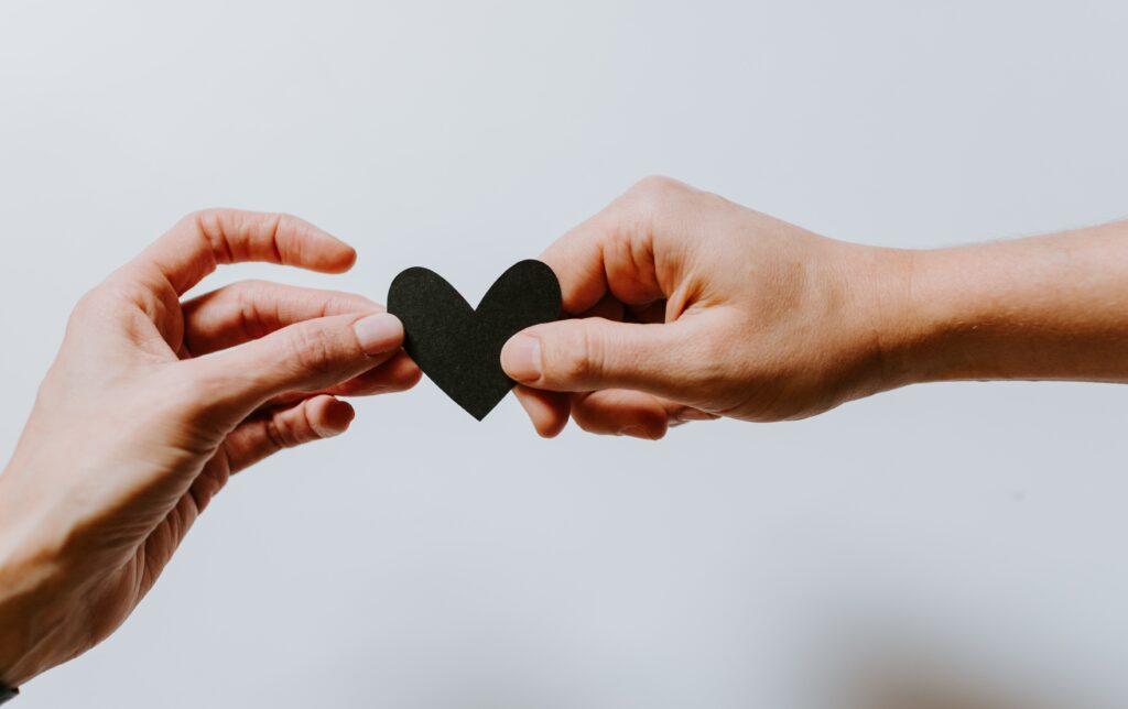 Hands passing a heart