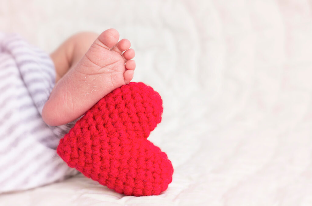 Baby feet with a red heart
