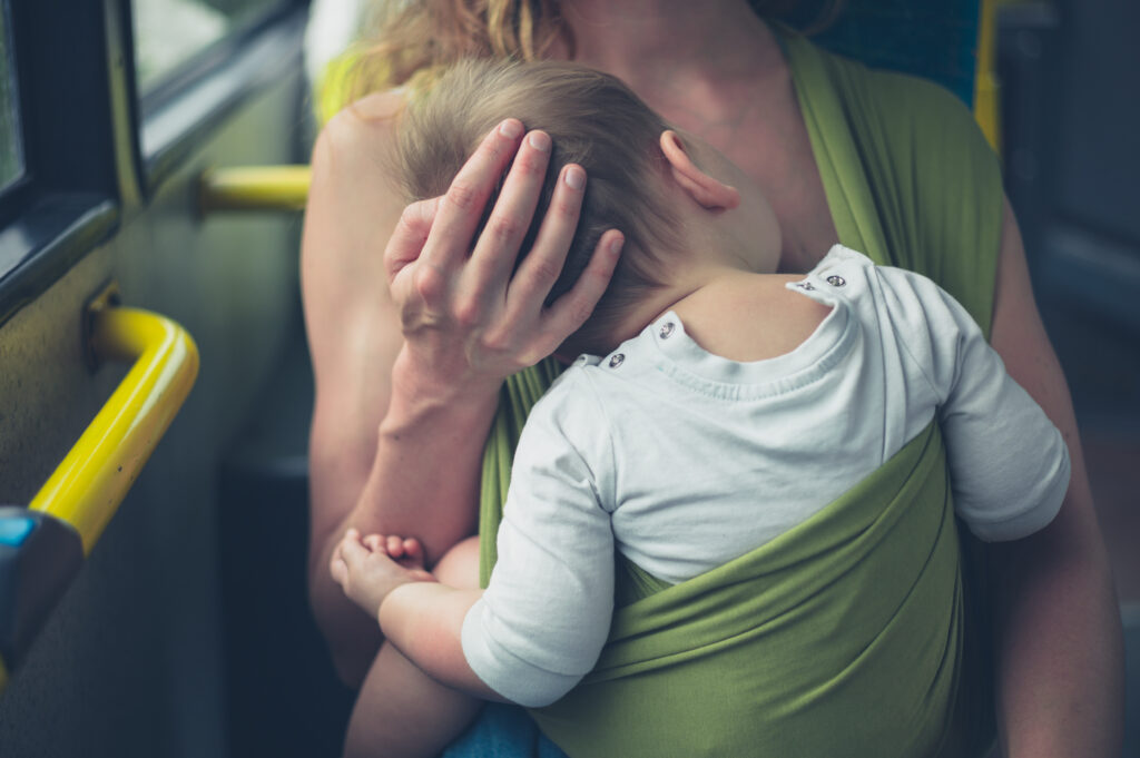 Mother riding a bus while babywearing