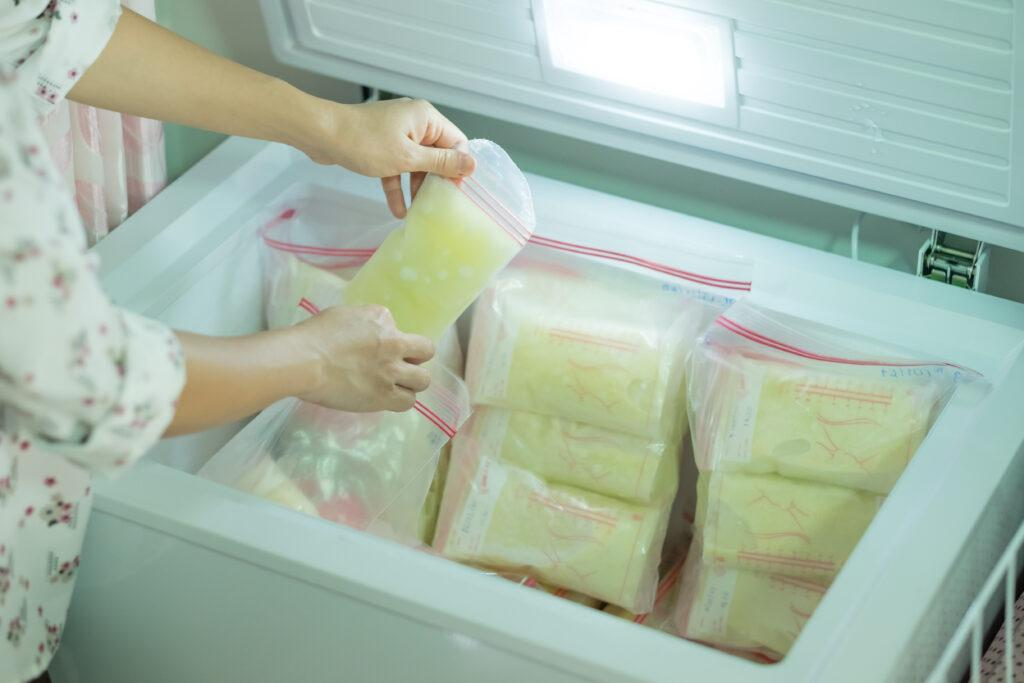 Woman leaning over freezer filled with milk bags.