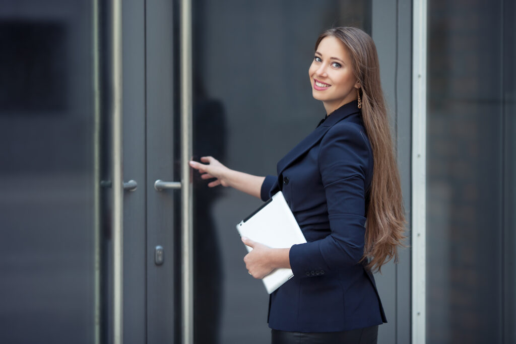 Woman in business attire opening a door.