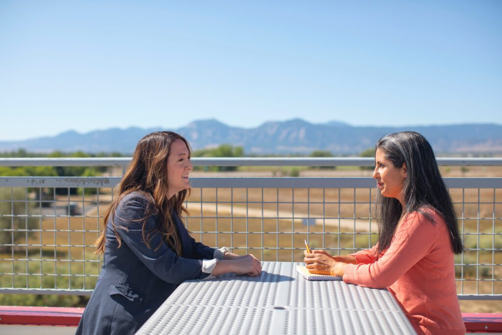 Two women in conversation at outdoor table with mountains in background.
