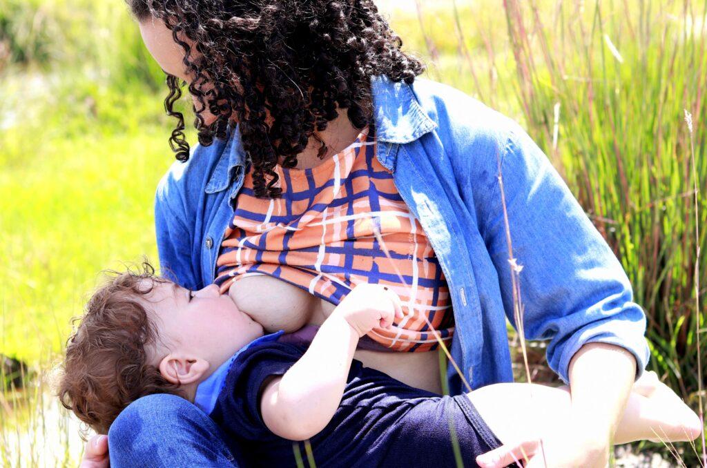 Brunette woman in blue shirt breastfeeding in a field of green grass.