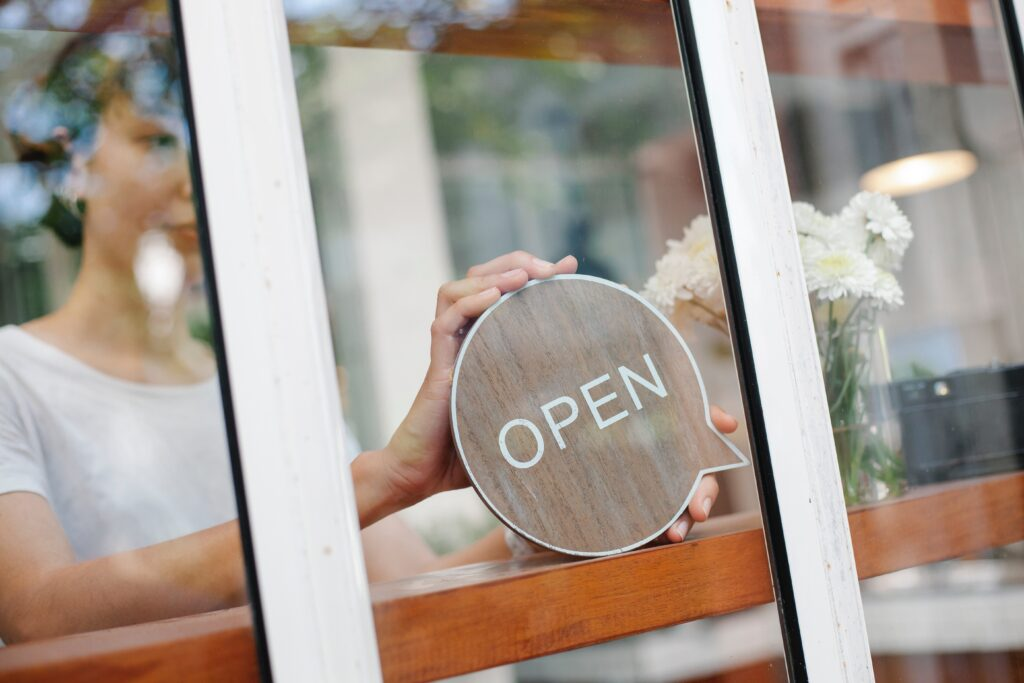 Woman putting open sign in front window.