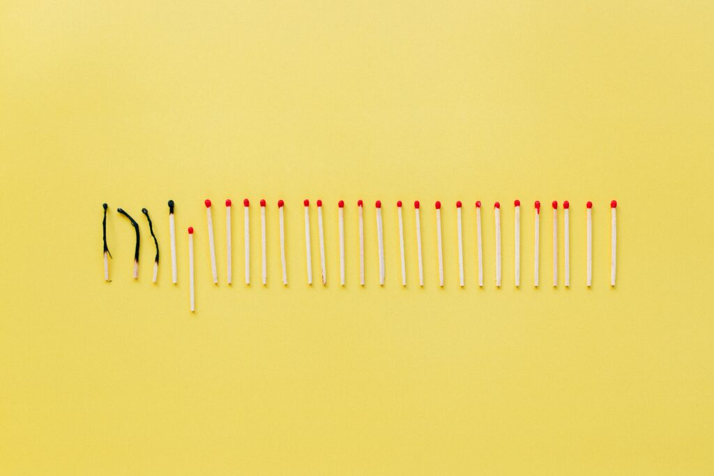 Yellow background with row of matches, some burned out.