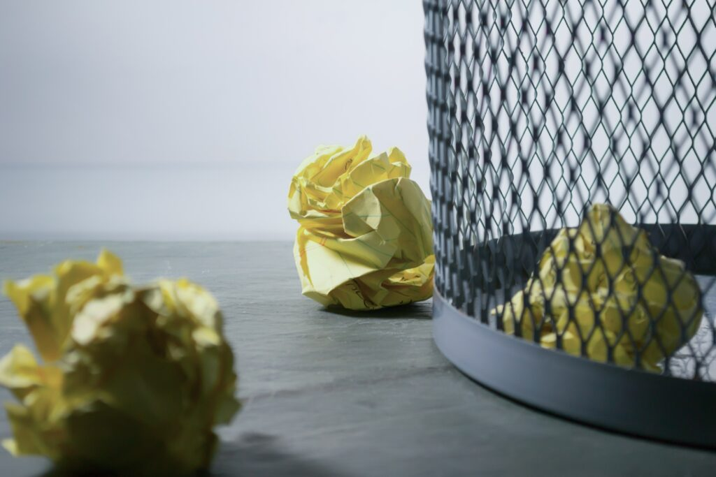 Wire waste basket with crumpled yellow paper.