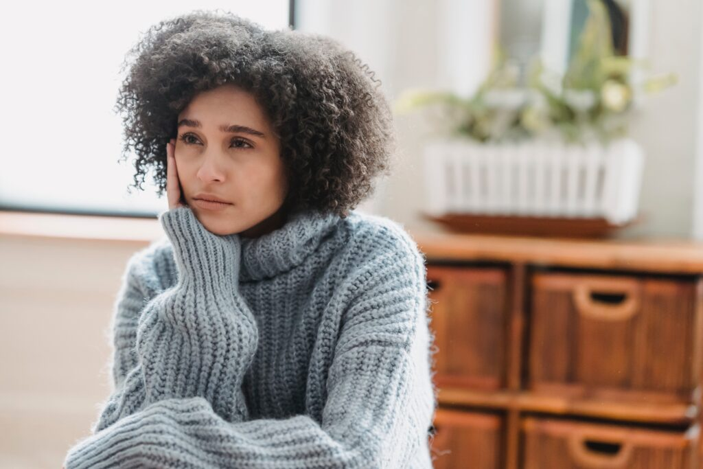 Woman in blue-gray sweater looking of into distance.
