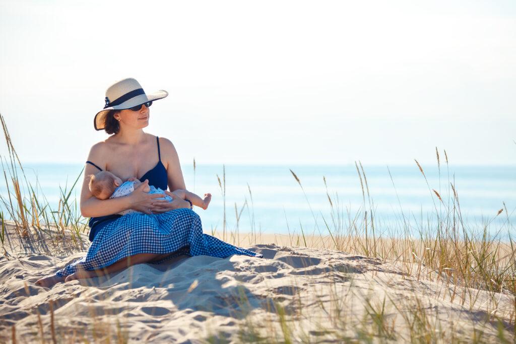 Woman in straw hat sitting on sunny beach breastfeeding.