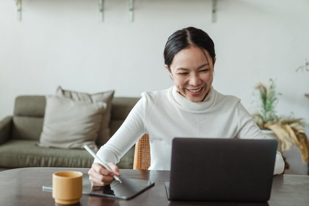 Woman in white sweater working on a laptop.