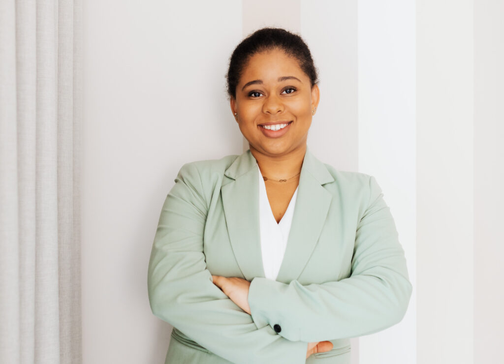 Woman in green blazer up standing against a striped wall.
