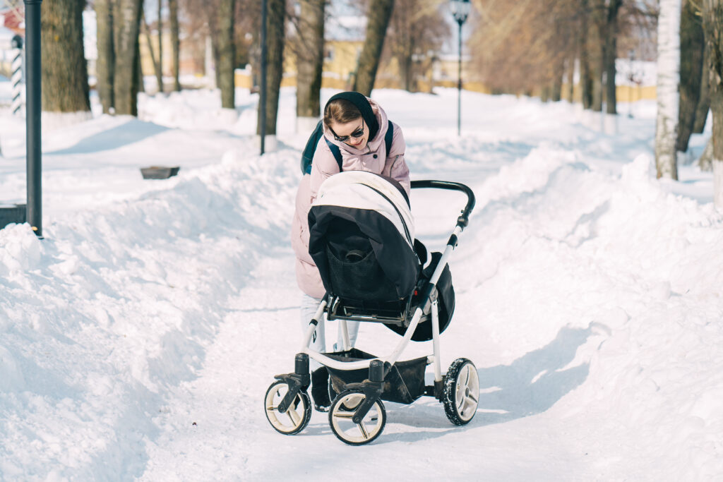 Woman with stroller on snow-covered sidewalk.