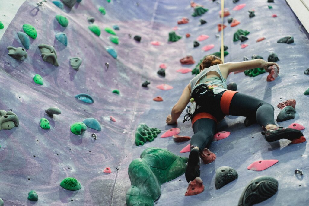 Woman climbing up rock wall obstacle.