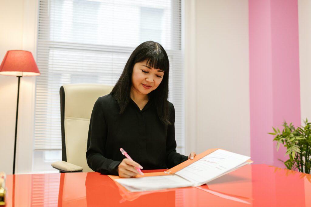 Woman sitting at orange desk completing paperwork.