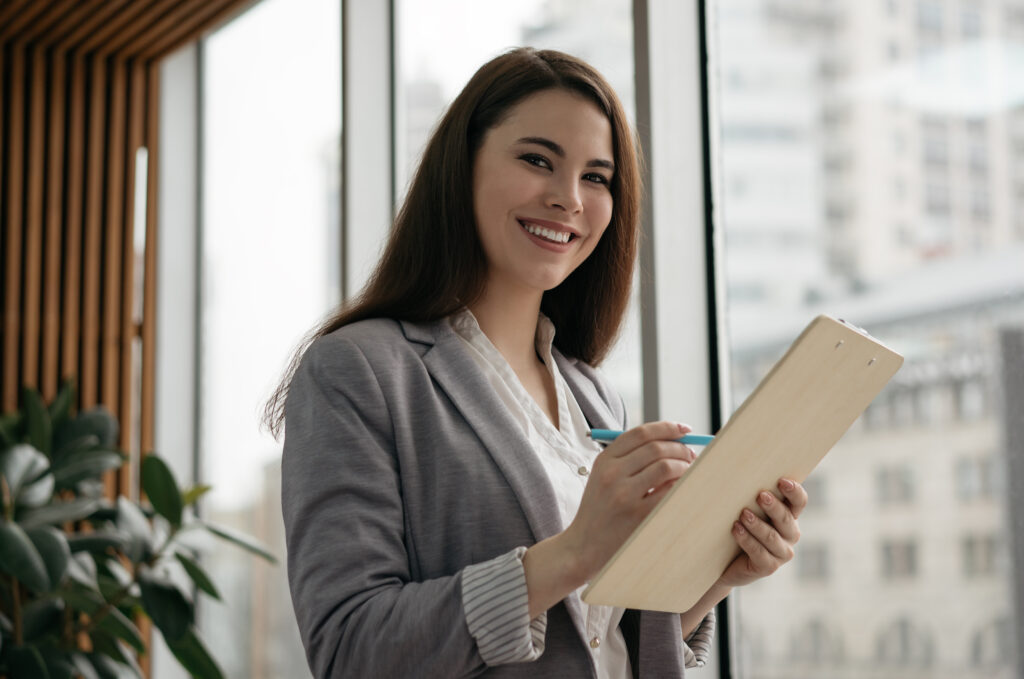 Woman in gray blazer with a clipboard.