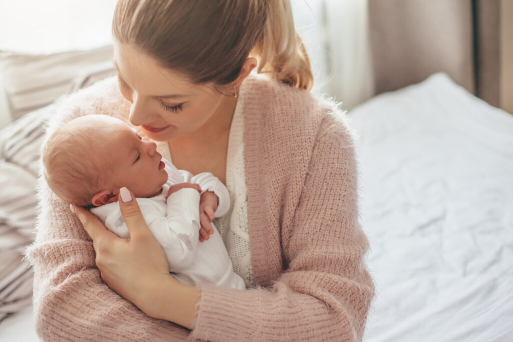 Mother in pink sweater holding newborn infant on hospital bed.